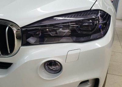 Бронирование фар автомобиля BMW X5 полиуретановой пленкой Stek с эффектом затемнения