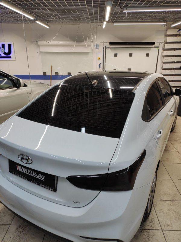 Оклейка крыши автомобиля Hyundai Solaris пленкой Oracal 8300 черный глянец и тонировка задних фар