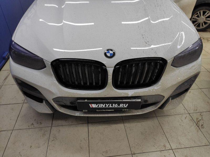 Оклейка решетки радиатора черной глянцевой пленкой и бронирование фар пленкой Stek — BMW X3